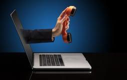 Hand med telefonen som kommer ut ur en bärbar dator royaltyfri foto