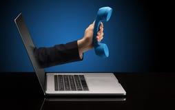 Hand med telefonen som kommer ut ur en b?rbar dator fotografering för bildbyråer