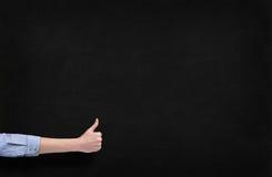 Hand med tummen upp över svart tavla Fotografering för Bildbyråer
