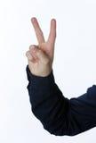 Hand med två fingrar upp i freden eller segern Arkivbild
