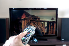 Hand med TVfjärrkontroll royaltyfria bilder