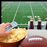 Hand med TVfjärrkontrollen, öl, chiper och fotboll Royaltyfri Bild