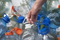 Hand med vattenflaskor Arkivbilder
