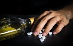 Hand med vit preventivpillerar och whisky Royaltyfri Fotografi