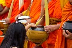 Hand, medan satta matofferings i en buddistisk munks allmosa bowlar f Royaltyfri Foto