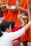 Hand, medan satta matofferings i en buddistisk munks allmosa bowlar f Arkivfoto