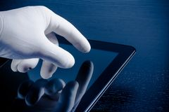 Hand in medical glove touching modern digital tablet pc Royalty Free Stock Image