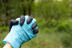Hand in medical gloves on a blurry green background in the street