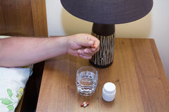 Hand with medicine closeup. Hand with medicine and a glass of water on the nightstand Royalty Free Stock Photo