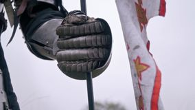 Hand knight`s gauntlet that holds the flag. Hand in medieval armor holds the flag stock footage
