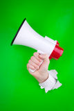 Hand and megaphone. Bright green paper background with white torn hole from which a hand holding a megaphone is emerging Royalty Free Stock Photography