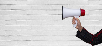 Hand with a megaphone in front of an empty white brick wall Stock Photography
