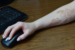 Hand with mehandi  drawing on the mouse. Hand of the young girl with the mehandi on a mouse Royalty Free Stock Images