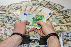 Hand men is in handcuffs holding money Stock Photography