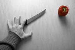 Hand, Messer und roter Pfeffer Lizenzfreie Stockbilder