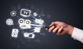 Hand met afstandsbediening en media pictogrammen stock foto's