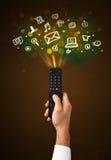 Hand met afstandsbediening en sociale media pictogrammen Stock Fotografie