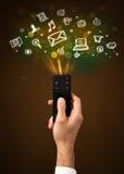 Hand met afstandsbediening en sociale media pictogrammen Stock Foto's