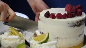Hand met de aardbei van messenbesnoeiingen Bessen op witte kokende raad Verse ingrediënten voor een dessert Chef-kok die in werke stock videobeelden