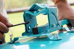 Hand met de moersleutel die blauw materiaal herstellen Royalty-vrije Stock Foto's
