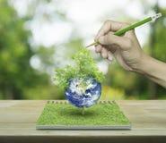 Hand met de planeet van de potloodtekening en boom van een open boek op wo Stock Afbeeldingen