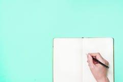 Hand met een lege blocnote met pen op een blauw Royalty-vrije Stock Afbeelding