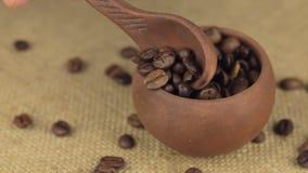 Hand met een lepel om de koffieboon van een roterende kleipot te gieten stock video