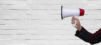 Hand met een megafoon voor een lege witte bakstenen muur Stock Fotografie