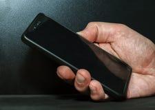 Hand met een mobiele telefoon Stock Foto