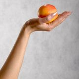 Hand met een perzik Royalty-vrije Stock Foto