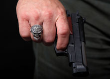 Hand met een ring in de vorm van een schedel die een pistool houdt Stock Fotografie