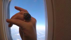 Hand met een ring dichtbij de patrijspoort stock videobeelden