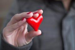 Hand met een rood hart stock afbeeldingen
