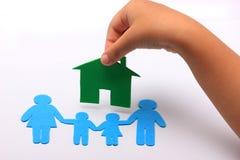 Hand met familiepictogram en groen huis Stock Afbeeldingen