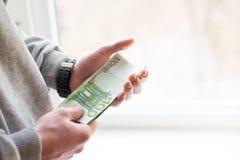 Hand met geld een paar honderd euro in bankbiljetten royalty-vrije stock afbeeldingen