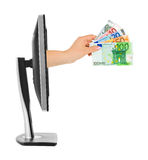 Hand met geld en computermonitor Stock Afbeeldingen