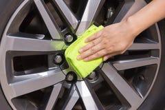 Hand met gele microfiberdoek die grote maximum auto schoonmaken stock fotografie