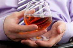 Hand met glas cognac stock fotografie