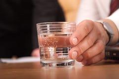 Hand met glas water = CLO Royalty-vrije Stock Foto's