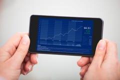 Hand met Grafiek op Mobiele Telefoon Royalty-vrije Stock Afbeeldingen