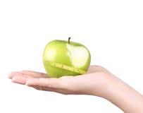 Hand met groene geïsoleerder appel Royalty-vrije Stock Afbeeldingen