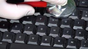 Hand met handschoenen en stethoscoop op toetsenbord Het concept van de computerdiagnostiek stock footage