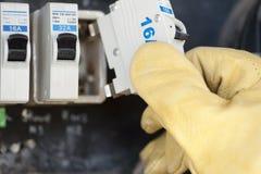 Elektricien met elektrische zekering bij schakelaarraad stock foto