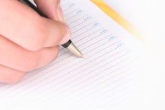 Hand met het handvat, dagelijks logboek, document Royalty-vrije Stock Foto's