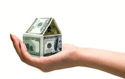 Hand met huis van bankbiljetten royalty-vrije stock afbeeldingen