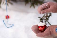 Hand met Kerstmisdecoratie Kleding op Kerstboom Stock Foto