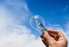 Hand met lightbulb op blauwe hemel Royalty-vrije Stock Foto
