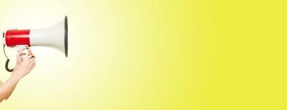 Hand met megafoon en gele achtergrond Stock Foto