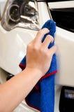 Hand met microfiberdoek die een auto afvegen Stock Foto's