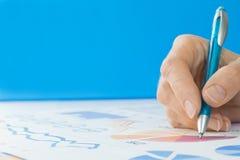 Hand met Pen Editing Graphs Royalty-vrije Stock Afbeeldingen